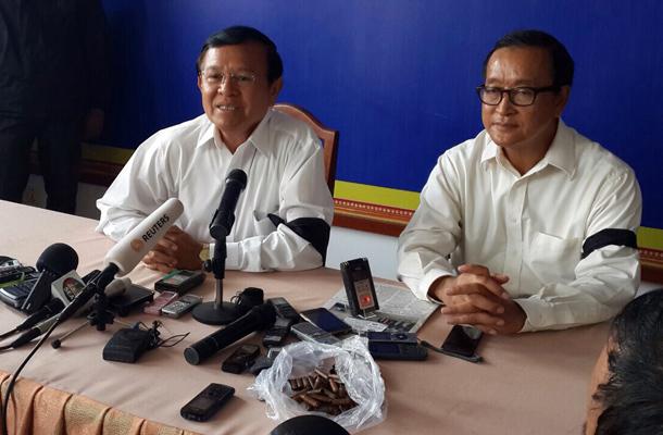 Pressekonferenz mit Trauerflor: Oppositionsführer Sam Rainsy und Kem Sokha zeigten sich am Samstag solidarisch mit den Opfern vom Freitag. Mittlerweile wurde gegen beide ein rein politisch motivierter Haftbefehl ausgestellt. (Foto: PRKN)
