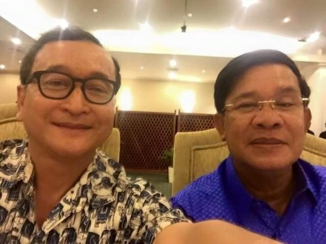 """Ein Selfie ist eigentlich auch in Kambodscha nichts Besonderes mehr, aber dies wird vielleicht eines Tages in die Geschichtsbücher eingehen: Sam Rainsy und Hun Sen unterstreichen mit diesem Schnappschuss eindrucksvoll, dass sie es ernst meinen mit ihrem """"Culture of Dialogue"""" – zumindest auf der zwischenmenschlichen Ebene. Am Samstag, als dieses Foto entstand, trafen sich beide zu einem gemeinsamen Abendessen im Hotel Cambodiana, im Schlepptau nicht nur ihre Gattinnen, sondern alle zurzeit greifbaren Sprösslinge. Ein Familientreffen der besonderen Art also – wo das noch hinführt? Jedenfalls nicht zum Ende der politischen Gegensätze: Die heutige Verabschiedung des hochkontroversen """"NGO-Gesetzes"""" boykottierten sämtliche Abgeordnete der Opposition. Aber darüber soll am Samstag nicht gesprochen worden sein, jedenfalls """"nicht vor den Kindern"""", wie ein Sprecher der regierenden Kambodschanischen Volkspartei erklärte. (Foto: Sam Rainsy)"""